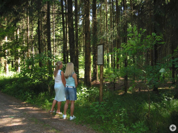 Zwei Wanderinnen vor einem Hinweisschild